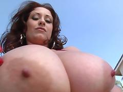 Dynamic brunette oiling her big tits before giving out titjob