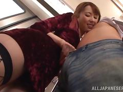 Doting Japanese pornstar in fishnet stockings delivers a handjob in public