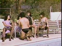 Brunettes sitting poolside harass guy on a leash