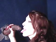 Kinky redhead with a hot body sucking a big black cock through a glory hole