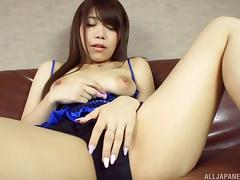 Ardent and solo Japanese slut lies on the couch and teases her muff using a vibrator