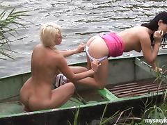 Lesbian girlfriends get busy in a boat out on a lake