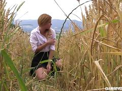 Out in a field of wheat she pulls her panties aside and fingers