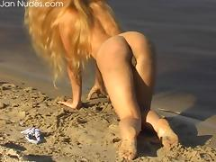 Blonde teen beauty on the beach plays with her bald pussy