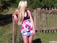 Blonde in the backyard sits in the grass and masturbates