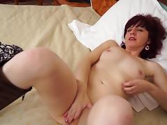 Redhead solo model stripteasing seductively while displaying her natural tits