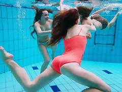 Three lovely playgirls strip out of their clothes in the pool