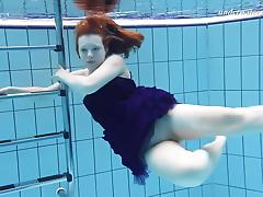 Russian redhead babe displaying her shaved pussy when swimming