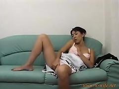 Cute Asian chick sits on the couch and gets naked to toy he
