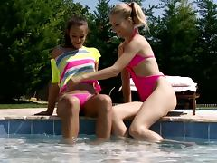 Two sexy babes fingering each other near a swimmimg pool