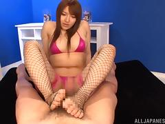 Japanese bitch gives a titjob and a footjob to some horny dude