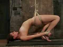 The ropes make her be arched and suspended