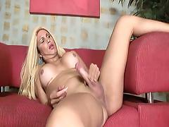 This blonde shemale is laying with her legs spread, jerking her cock and showing those tits