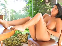 Curvy brunette Romi plays with her fascinating natural tits indoors