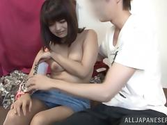 An Asian girl with juicy boobs gets fucked in a missionary pose