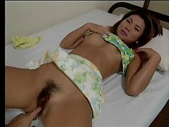 Cute Japanese girl squirms and wriggles as her hairy cunt is fingered on bed