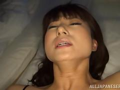 Lustful Asian milf pleases herself with fingering on a bed